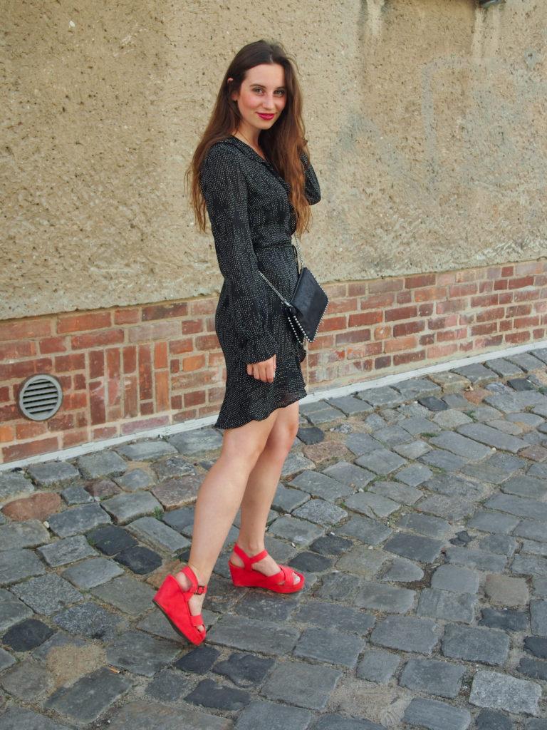 Bring Farbe ins Spiel: schwarzes Wickelkleid mit orangenen Sandalen!